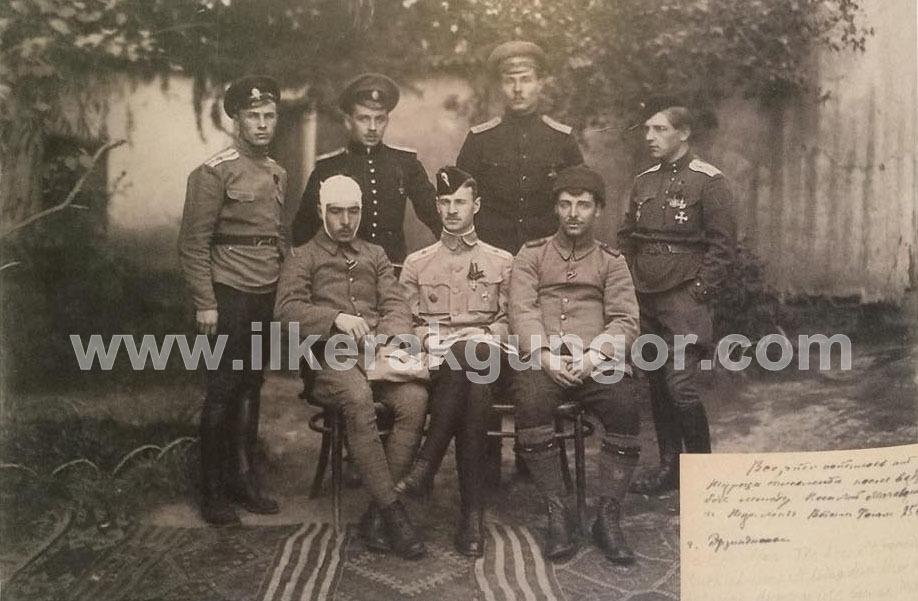 Pilot Astsubay Vecihi Hürkuş (sol başta oturan) ve Rasıt (gözlemci) Üsteğmen Bahattin Bey (sağ başta oturan) kendilerini düşüren Rus hava filosunun askerleri ve filo komutanıyla (ortada oturan) görülüyor.